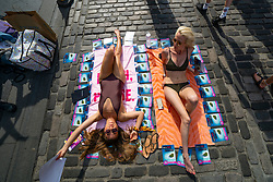 Edinburgh, Scotland, UK. 3 August 2019. On the opening day of the Edinburgh Festival Fringe these two young women were sunbathing on the Royal Mile and handing out flyers to their show Got a Text: A Musical Parody