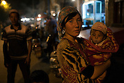 Kashgar: A local Uighur woman and her son at night on the streets surround Id Khar mosque in Kashgar...Despite the migration of millions of Han Chinese to the western part of the Xinjiang Uighur Autonomous Region, the Uighur community continue to practice their muslim culture and resist the suppression of their cultural and religious traditions by the Chinese government....The chinese government has been criticised for the redevelopment of the old city, which has involved the destruction of many of the old houses in the town that were built without regulation, officials claiming them to be overcrowded and uncompliant with earthquake codes...Many in the chinese government believe Kashgar to a breeding ground for Uighur separatists, who Beijing claim to have links to terrorism...The european parliament has called for a halt to the cultural destruction of Kashgar, suggesting that Kashgar be added tot he UNESCO World heritage 'Silk Road' project, and calling on the chinese government to develop a genuine Han-Uighur dialogue to adopt more inclusive and comprehensive economic policies in Xinjiang in order to protect the cultural identity of the Uighur population..©JTanner/July 2011