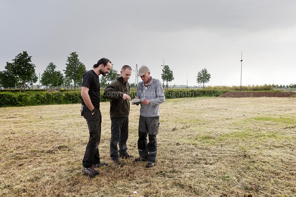 Jean étudie avec Arnaud et Romuald, les responsables de l'organisation, l'emplacement où se fera l'installation.
