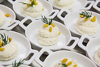 "MILANO, ITALY - 1 MARCH 2016: Amuse-bouches (cheese mousse  with mustard, curry crunchies and dill) are served as welcome snack together with a glass of prosecco to all the customers of the ""InGalera"" restaurant upon their arrival, here in the Bollate prison in Milan, Italy, on March 1st 2016.<br /> <br /> ""InGalera"" (which translates in English as ""InJail"") is the first restaurant located inside a prison and offering high-quality cooking to the public and a future to the inmates. It was inaugurated last October inside the Bollate prison in Milan. It is open five days a week for lunch and dinner, and seats 55 people. There are 9 people involved in the project, including cooks and waiters, all regularly employed and all inmates of the prison, apart from the chef and the maître d'hôtel, recruited from outside to guarantee the high quality of the food served. The restaurant is a project of the co-operative ABC La Sapienza - that operates inside the prison and provides more than 1,000 meals three times a day with the help of inmates they've hired - and of PwC, a multinational operating in the field of corporate consultancy. The goal of this project is to follow prisoners in rehabilitation process of social inclusion.<br /> <br /> The Bollate prison is already known for being a good example of penitentiary administration. The inmates are free to move around from one area to the other inside the prison (their cells open at 7:30am and close at 9pm) to go study, exercise in a gym, or work (in a call center, as scenographers, tailors, gardeners, cooks, typographers, among others)  in one of the 11 co-operatives inside the prison or in one of the private partnering businesses outside the prison. The turnover of the co-operatives that work inside the prison was €2mln in 2012."