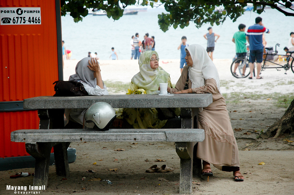 Three elderly ladies having a chat on a weekend at East Coast Park, Singapore