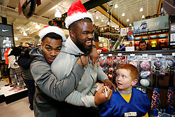 "Kansas City Chiefs players Charcandrick West and Dontari Poe joke around with members of the Football and Cheerleading Club of Johnson County as they shop for items on their ""wish list"" at the ""Sports Matter"" Holiday Shopping event hosted by DICK'S Sporting Goods on Thursday, Dec. 17, 2015, in Leawood, KS. (Colin E. Braley/AP Images for Dick's Sporting Goods)"