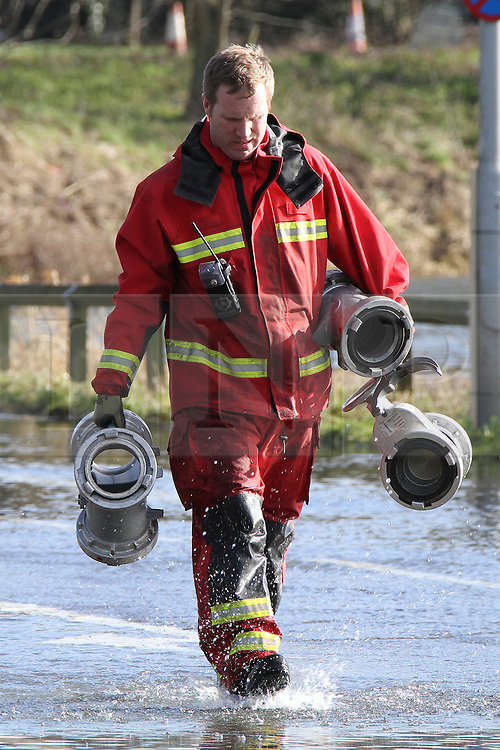 © Licensed to London News Pictures. 17/02/2014. Egham, UK. A firefighter carries parts of a hose system. Fire And Rescue Services Set up pumps to clear the A308 Windsor Road near Runnymede. Photo credit : John Maxwell-Roberts/LNP