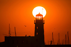 © Licensed to London News Pictures. 18/07/2017. Scarborough UK. The sun rises this morning behind Scarborough lighthouse on the east coast of Yorkshire on another hot day for the UK. Photo credit: Andrew McCaren/LNP