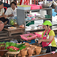 Woman Preparing Food at Taling Chan Floating Market near Bangkok, Thailand <br />