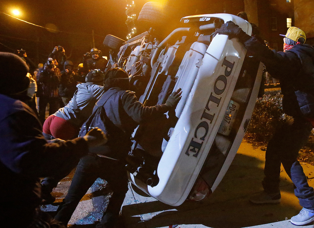 Protesters flip a Ferguson police car set on fire by protesters in Ferguson, Missouri, November 25, 2014.  REUTERS/Jim Young
