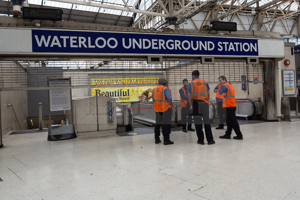 © Licensed to London News Pictures. 06/08/2015. London, UK. Staff stand at the closed entrance to the tube station at Waterloo station in London. A tube strike today has closed the TfL London Underground network as members of four unions take industrial action for the second time in a month because of a deadlocked dispute over plans to launch a new all-night tube train service next month. Extra busses have been laid on to help commuters get to work. Photo credit : Vickie Flores/LNP