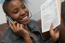 Teenage girl talking on the phone after opening exam results,