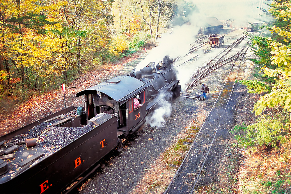 On a beautiful Saturday in Fall, here are switching maneuvers in the East Broad Top Railroad Rockhill yard as the brakeman/fireman is about to flip to the other track and the engineer waits with his hand on the throttle. The big tea kettle just hisses away.<br /> <br /> I had climbed high onto the coaling tower above the tracks to take this shot on slide film years ago, scruffing my way up the steep earthen bank using small scrub trees as handholds. It was a great vantage point, and I was completely unseen by the crew or any train passengers in the cars thirty feet below.<br /> <br /> #14 is a 2-8-2 and was built by the Baldwin Locomotive Works of Philadelphia in 1912. This locomotive and her five narrow gauge sisters were all Baldwin built between 1911 and 1920, and all are still on the property.