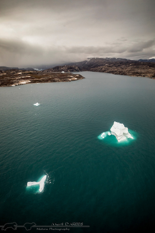 Two small icebergs in a Greenlandic fjord.