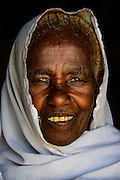 Friendly old woman standing in a door frame near Keren, Eritrea