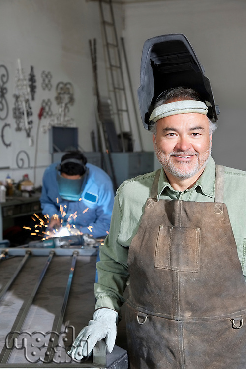 Portrait of a happy mature man wearing protective mask with young male welding in background