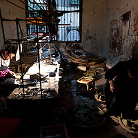 Chongqing, China - 31 December 2010: a run  down factory where two workers manufacture shoes. According to a report published by Bank of America Merrill Lynch's David Cui, titled 'Not So Trivial Facts', China has produced in 2010 a total of 12.6 billion pairs of shoes which means 9.4 pairs of shoes per person, compared with 1.3 pairs in the rest of the world (63.0 percent of global total).