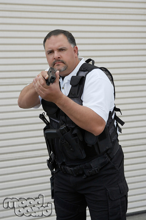 Portrait of security guard in bulletproof vest holding gun