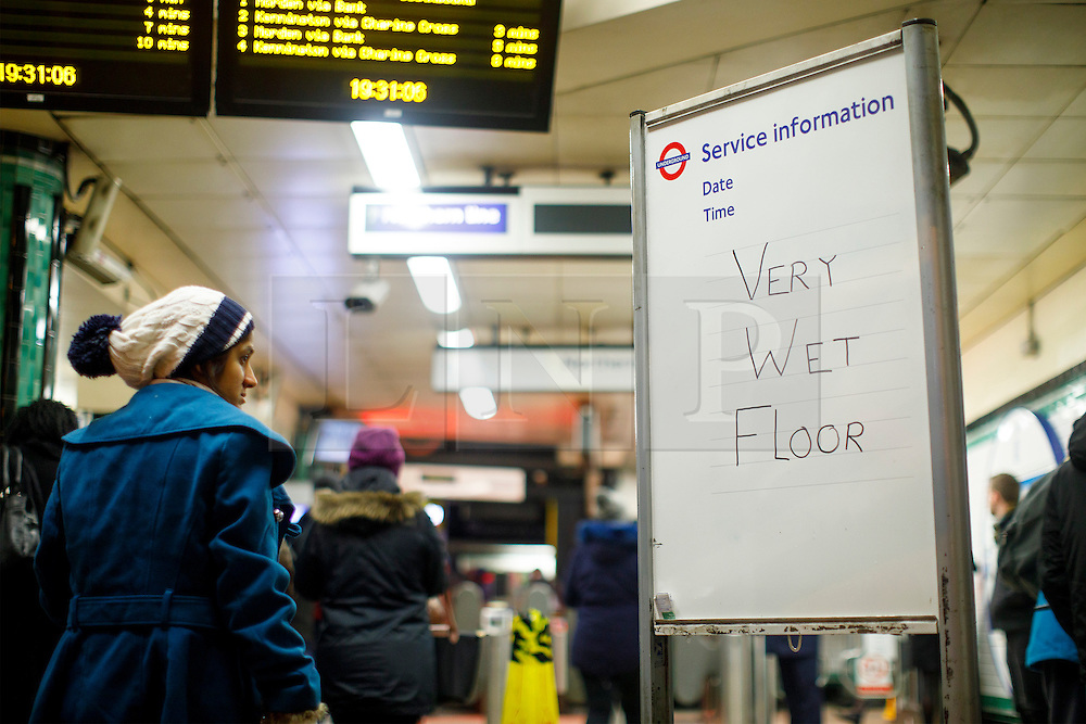 """© Licensed to London News Pictures. 12/01/2017. London, UK. A sign reads """"Very Wet Floor"""" at the entrance of Camden Town tube station as people commute in north London whilst the first snow of the season starts to fall in London on Thursday, 12 January 2017. Photo credit: Tolga Akmen/LNP"""