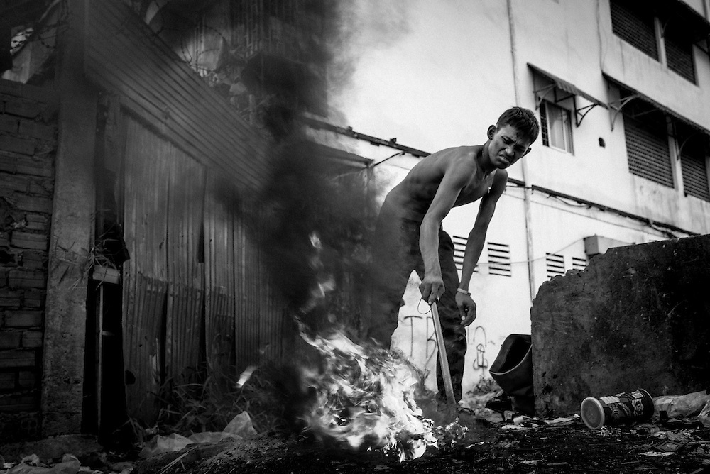 A scavenger burns the rubber coating off copper wires so he can sell the pure metal. The community of Borei Keila in Phnom Penh was once home to hundreds of families before land developer Phanimex bought the property rights to the area and forcefully evicted the residents who refused to accept their compensation package. Those who remained were forced to squat in the remains of the buildings, living in slum-like conditions and without access to plumbing or public electiricity.
