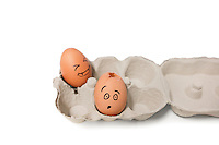 Carton of brown eggs with one cracked egg