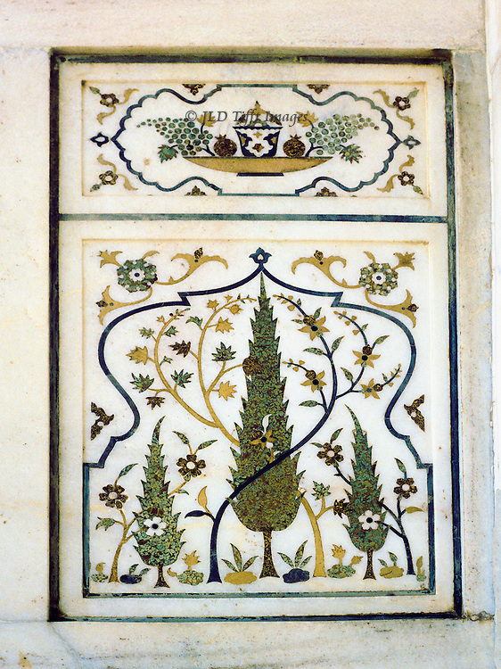 Marble pietra dura wall panel in the Itimad ud Daulah tomb, Agra.  This monument is a forerunner of the Taj Mahal, which see.  This panel shows a stylized cypress, flowers, and above a dish of fruit, set in a plain border.