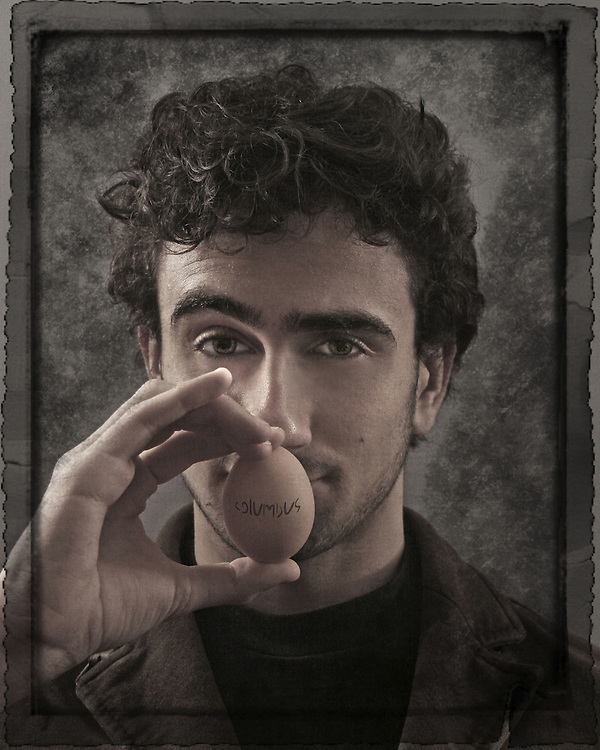 A young holding an egg infront of his face