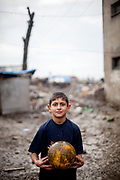 A boy with a football is posing for a portrait at the Roma settlement in Moldava nad Bodvou. From about 800 inhabitants of the segregated settlement 'Budulovska Street' are roughly 392 children up to the age of 16 years (2014) .