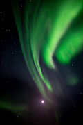 Multiple curtains of northern lights with the moon in the lower part of the image. (Photo by Travel Photographer Matt Considine)