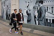 Two men walk past a fashion poster showing a fashion boy and girl and St Paul's Cathedral.