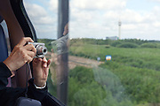 person making pictures from the train with point and shoot camera Holland near Rotterdam