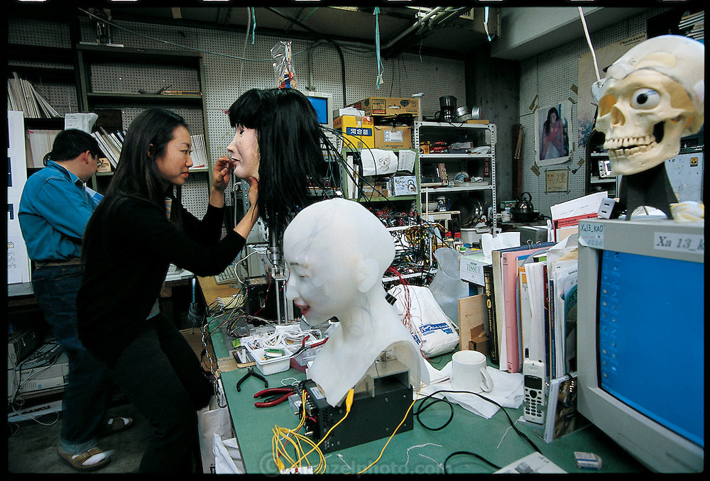Trying to concentrate in a crowded, busy workspace, graduate student Harumi Ayai pats makeup onto the immobile features of a face robot in the Hara-Kobayashi Laboratory. This machine, the first face robot built in the lab, has a single camera in its left eye. Notwithstanding the relative simplicity of its design, the machine was able to smile when people approached it. Although rapidly superseded by later models, the lab went through three generations in a few years, the robot is still being studied. Japan. From the book Robo sapiens: Evolution of a New Species, page 78-79.