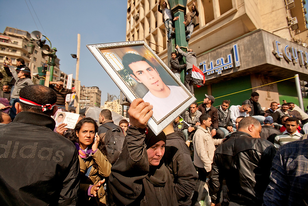 Cairo, Egypt - February 11th, 2011 - A woman carries the picture of a loved one while Egyptians demonstrate in Tahrir Square in downtown Cairo, in a concerted effort to draw attention to past police brutality, poverty and the rising cost of living; in spite of some deaths and many injured caused by police heavyhandedness.  Slogans were shouted against the president of Egypt, Hosny Mubarak; urging his government to step down after being in power for 30 years. Soon after this event, President Mubarak relinquished his presidency to the control of the Egyptian army. Photo by Wally Nell