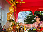 14 APRIL 2019 - DES MOINES, IOWA: A woman sprinkles scented water on a statue of the Buddha during Lao New Year, also called Songkran,  observances at Wat Lao Buddhavath in Des Moines. Several thousand Lao people live in Des Moines. Most came to the US after the wars in Southeast Asia. Songkran is celebrated in Theravada Buddhist countries (Sri Lanka, Myanmar, Thailand, Laos, and Cambodia) and in Theravada Buddhist communities around the world.       PHOTO BY JACK KURTZ