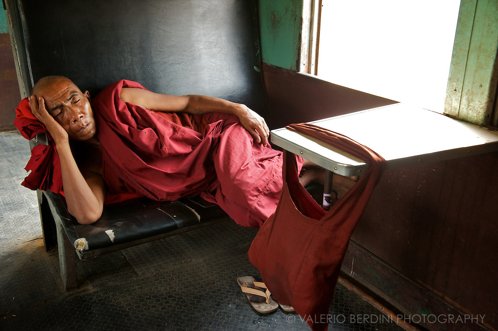 A monk (Bhikkhu) takes a nap on a one of the endless journeys of Burmese train. the ninth precept says monks should not sleep on luxurious, soft beds.