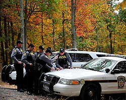 Troopers look at a map and discuss search areas. Police continue to search the heavily wooded terrain for fugitive Eric Matthew Frein on Oct. 3, 2014, near Canadensis, Pa. (Chris Post | lehighvalleylive.com)