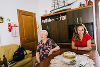 ACCIAROLI, ITALY - 14 SEPTEMBER 2018: Anna Vassallo (91) and her granddaughter Carmen are seen here in her living room in Acciaroli, a small fishing village in the municipality of Pollica, Italy, on September 14th 2018.<br /> <br /> To understand how people can live longer throughout the world, researchers at University of California, San Diego School of Medicine have teamed up with colleagues at University of Rome La Sapienza to study a group of 300 citizens, all over 100 years old, living in Acciaroli (Pollica), a remote Italian village nestled between the ocean and mountains in Cilento, southern Italy.<br /> <br /> About 1-in-60 of the area's inhabitants are older than 90, according to the researchers. Such a concentration rivals that of other so-called blue zones, like Sardinia and Okinawa, which have unusually large percentages of very old people. In the 2010 census, about 1-in-163 Americans were 90 or older.