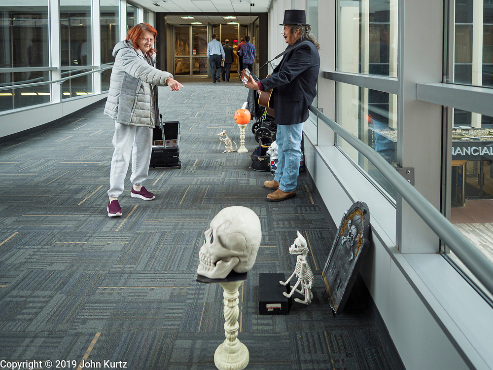 """30 OCTOBER 2019 - DES MOINES, IOWA: RANDY KONG, right, talks to a passerby who stopped while he was performing in the Des Moines Skywalk system. Kong said he's been busking for about nine years. He said he started when his band broke up and busking might be way to """"get a hot dog and a coke, and now it's turned into a career."""" He is a regular sight in the skywalk system. In October he hands out candy and sings Halloween themed songs while wearing a """"Phantom of the Opera"""" like mask. In December he does a Christmas themed show and in February he does a Valentines themed show.          PHOTO BY JACK KURTZ"""