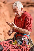 Jim Donini (age 72) taping up for another desert splitter in Long Canyon near Moab Utah.