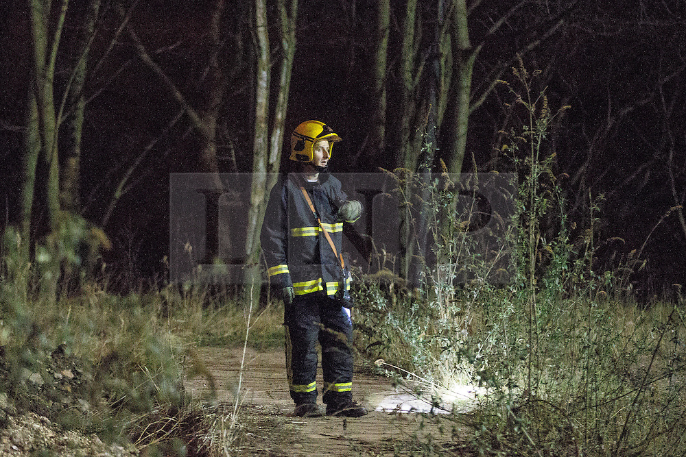 "© Licensed to London News Pictures . 15/03/2015 . Salford , UK . Fire crew examine the route from the nearby River Irwell to the scene of the fire . Roads are closed and people have been evacuated as a large fire burns at a unit within "" Junction Eco-Park "" in Clifton , Greater Manchester , this evening (Sunday 15th March 2015) . The smoke and flames can be seen for many miles . Forty fire fighters are at the scene working to control the blaze . Photo credit : Joel Goodman/LNP"