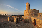 Towers of the 1st and 2nd fortresses, at Qal'at al-Bahrain, or Bahrain Fort or Portuguese Fort, built 6th century AD, once the capital of the Dilmun Civilisation, near Manama in Bahrain. The site consists of a tell or artificial mound 12m high containing 7 layers of archaeological remains dating from 2300 BC to the 18th century, topped with a medieval fortress. There is evidence of Kassites, Greeks, Portuguese and Persians, with burial sites, fortifications and residential areas. Qal'at al-Bahrain is listed as a UNESCO World Heritage Site. Picture by Manuel Cohen