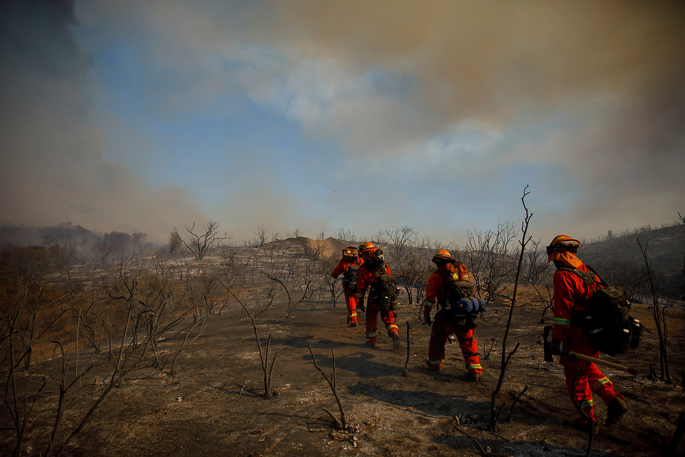 Inmate firefighters hike through a burned area to battle the Wildomar wildfire in the Cleveland National Forest on Thursday, October 26, 2017 in Wildomar, Calif. The fire started after a motorcycle crashed into a tree. © 2017 Patrick T Fallon