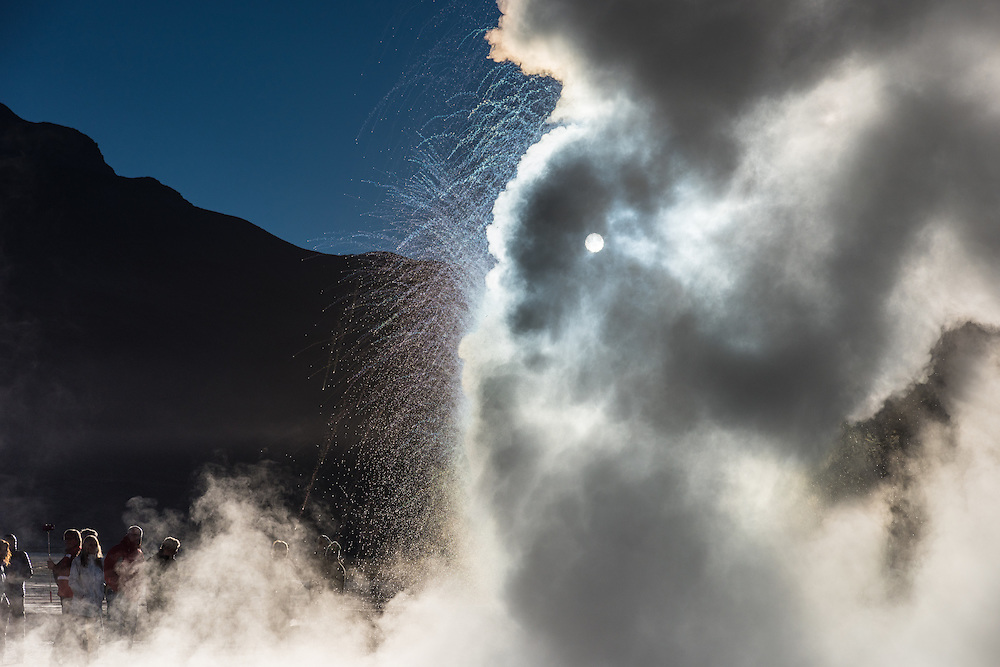 The sun rises over the mountain at sunrise as one of the biggest geysers blows out boiling hot steam, El Tatio, Chile.