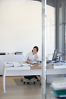 Businesswoman sitting at desk in office.