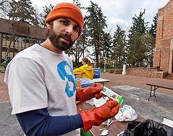 Nick Lorax holds one of the unopened snack bars he  found in trash during Garbology on Red Square, where grash from different locations is sorted to determine how much is recycleable or compostable at PLU on Tuesday, March 17, 2015. (Photo: John Froschauer/PLU)
