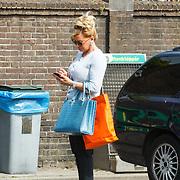 NLD/Amsterdam/20150521 - Conny Breukhoven druk telefonerend terwijl partner Eugene van Dun de auto stofzuigt