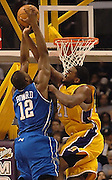 2.28.06--Los Angeles CA-Magic #12 Dwight Howard is fouled hard by Lakers #21 Ronny Turiaf in the second half of a in a game at Staples Center in Los Angeles. Daily News photo by John McCoy/Staff Photographer