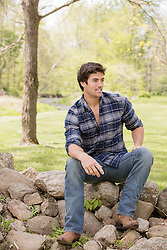 man in a plaid shirt sitting on a stone fence