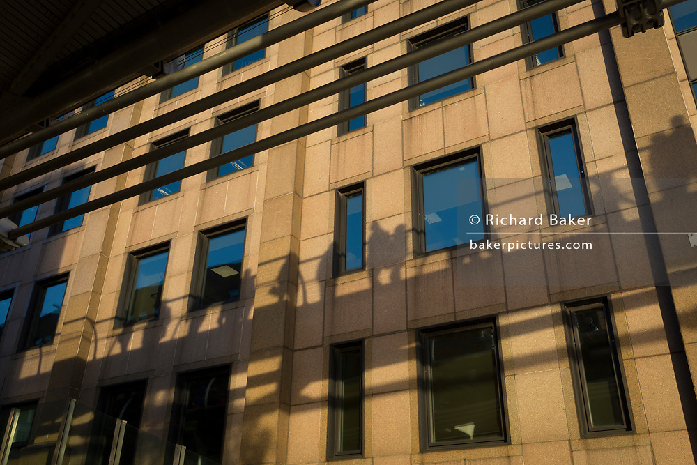 The shadows of pedestrians walking over the Millennium Bridge overhead, appear on the walls of offices, on 30th October 2017, in the City of London, England.
