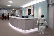 Honda Motor Co.'s humanoid robot ASIMO stands by the reception of an office during a media demonstration of Honda's new intelligence technologies, which enables the robot to act autonomously and perform uninterrupted services to office guests.