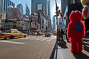 A guy dressed as the Elmo muppet waits for tourist people to take a photo on a corner of Times Square, Manhattan, New York