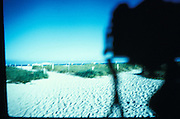 Distorted view of a beach with camera shadow.