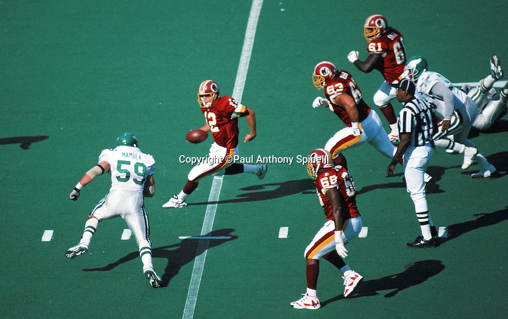 Washington Redskins quarterback Gus Frerotte (12) gets pressured by Philadelphia Eagles linebacker Mike Mamula (59) as he runs the ball in this general view overhead photograph taken during the NFL football game against the Philadelphia Eagles on Oct. 8, 1995 in Philadelphia. The Eagles won the game 37-34 in overtime. (©Paul Anthony Spinelli)