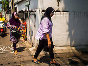 10 APRIL 2015 - BANGKOK, THAILAND: Thai Muslim women walk through a Muslim neighborhood near Ton Son Mosque in Bangkok. A Pew Research Center study recently released identified Islam as the fastest growing religion in the world. Masjid Ton Son was the first mosque in Bangkok, founded in 1688 during the reign of King Narai, of the Ayutthaya era. Muslims are about 5 percent of Thailand, but make up a bigger proportion of Bangkok. Thailand's deep south provinces are Muslim majority.    PHOTO BY JACK KURTZ